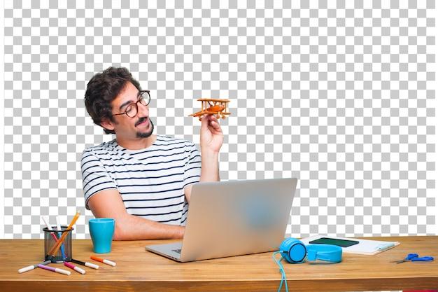 Junger verrückter grafikdesigner auf einem schreibtisch mit einem laptop und mit einer hölzernen fläche Premium PSD