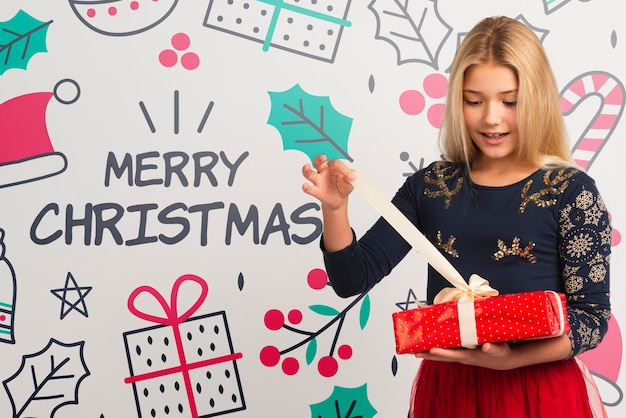 Junges mädchen, das geschenk auf weihnachten auspackt Kostenlosen PSD