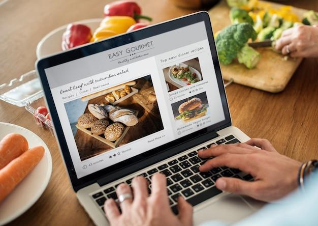 Kaukasischer mann, der einen laptop in der küche sucht nach rezepten verwendet Premium PSD