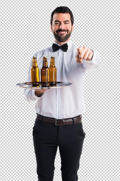 Kellner mit bierflaschen auf dem tablett nach vorne zeigend Premium PSD