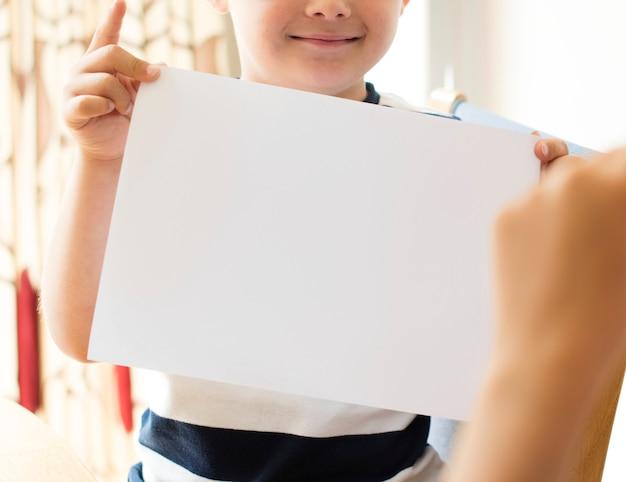 Kleiner junge mit einem leeren papiermodell Kostenlosen PSD