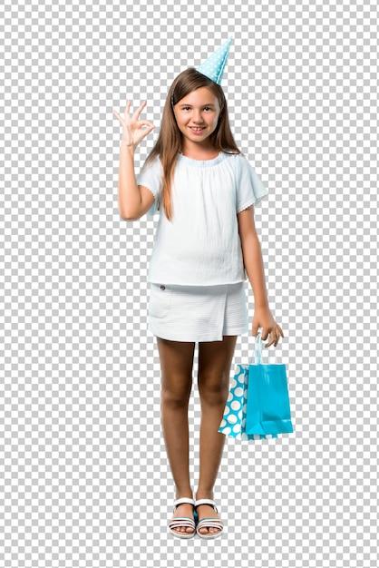 Kleines mädchen an einer geburtstagsfeier, die eine geschenktasche zeigt ein okayzeichen mit den fingern hält Premium PSD