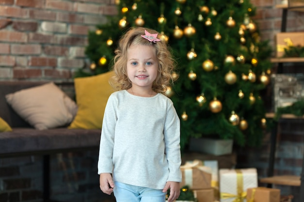 Kleines mädchen neben dem weihnachtsbaum, mit modellpullover für ihr design Premium PSD
