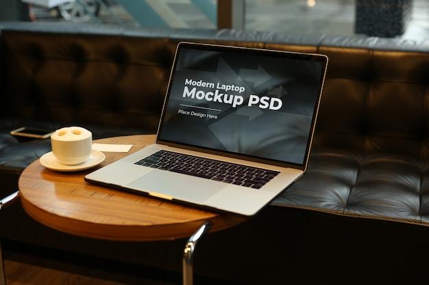 Laptop mit kaffee auf rundem tisch modell psd Premium PSD