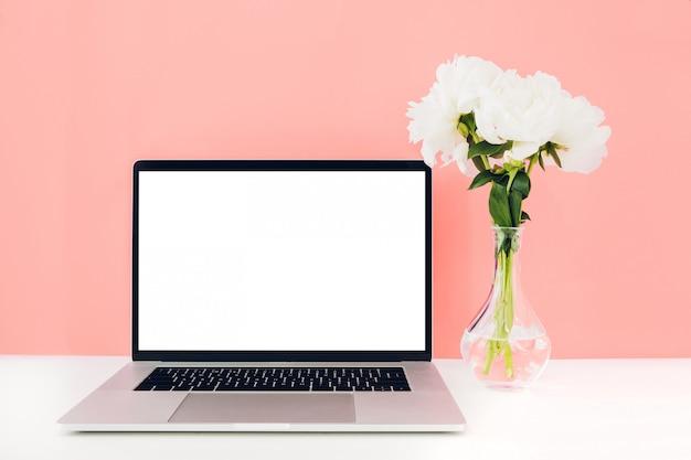 Laptop mit weißem leerem bildschirm und blumen in der vase auf tisch Premium PSD