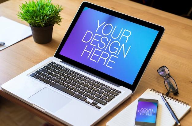 Laptop- und handy-modelle auf bürotisch Premium PSD