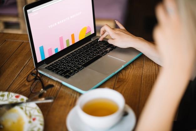 Laptopmodell mit frau auf holztisch Kostenlosen PSD