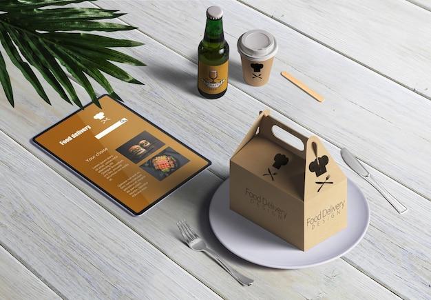 Lebensmittellieferung mit pappschachtel und menü auf holztisch Kostenlosen PSD