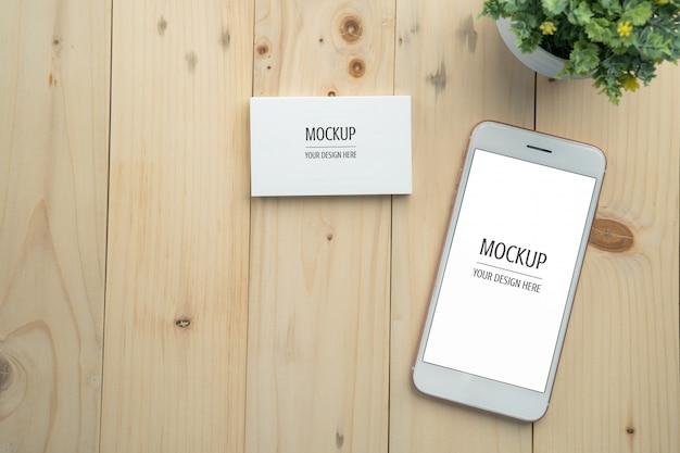 Leerer weißer bildschirm smartphone und visitenkartemodell auf hölzernem tabellen- und kopienraumhintergrund Premium PSD