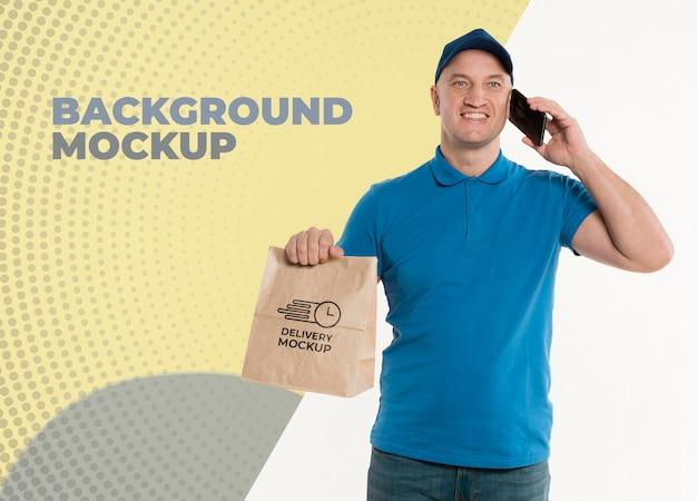 Lieferbote, der eine einkaufstasche hält, während er am telefon spricht Kostenlosen PSD