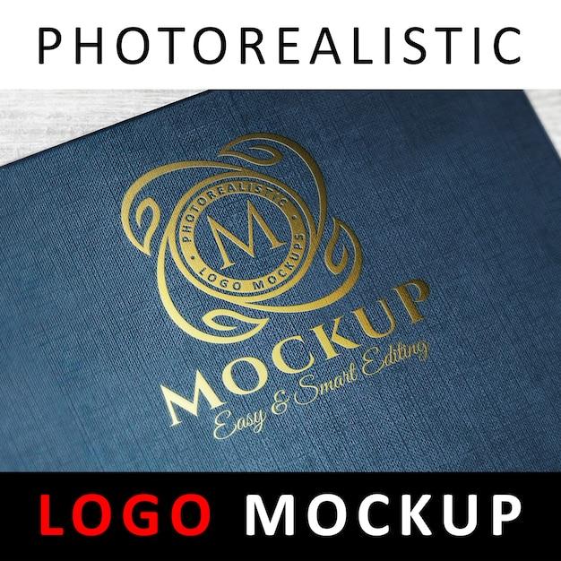 Logo mockup - goldfolie, die auf blauer strukturierter abdeckung stempelt Premium PSD