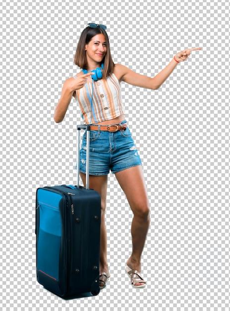 Mädchen, das mit ihrem koffer finger auf die seite reist und ein produkt beim lächeln darstellt Premium PSD