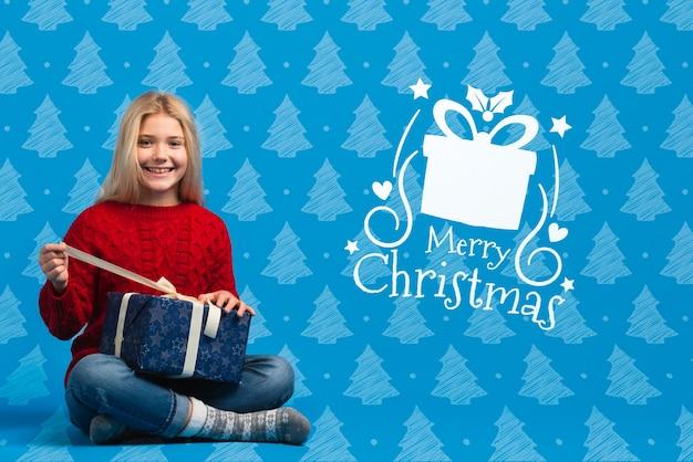 Mädchen kleidete im weihnachtsthematischen strickjackenöffnungsgeschenk an Kostenlosen PSD