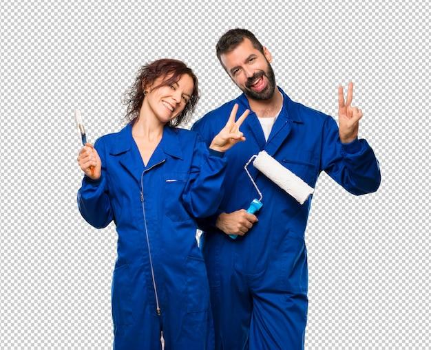 Maler, die victory-zeichen mit beiden händen lächeln und zeigen Premium PSD