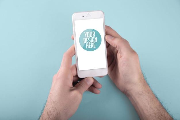 Mann, der ein weißes smartphone mit hellem blauem hintergrund beider hände verwendet Premium PSD