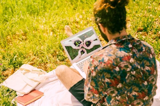 Mann, der laptopmodell in der natur verwendet Kostenlosen PSD