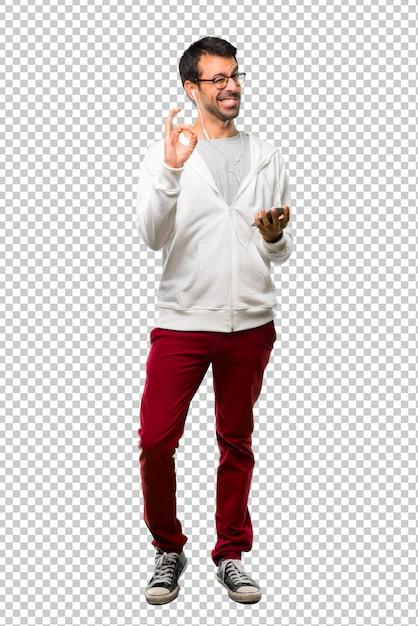 Mann mit brille und hörender musik, die ein okayzeichen mit den fingern beim blinzeln eines auges zeigt Premium PSD
