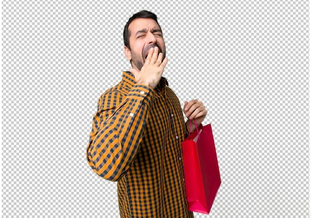 Mann mit einkaufstaschen gähnen und breiten mund mit der hand abdecken Premium PSD