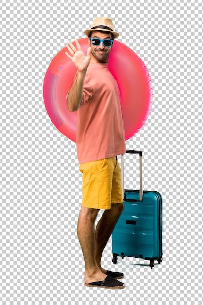 Mann mit hut und sonnenbrille auf seinen sommerferien begrüßend mit der hand mit glücklichem ausdruck Premium PSD