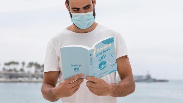 Mann mit maske auf straßenlesebuch Kostenlosen PSD