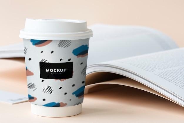 Mitnehmerkaffeetassenmodell auf einer tabelle mit einem offenen buch Kostenlosen PSD