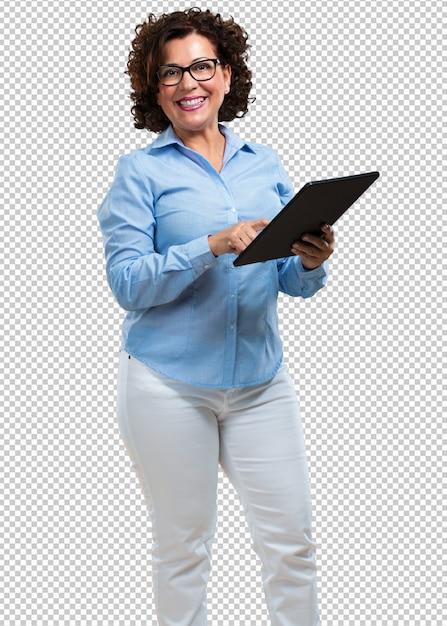 Mittlere greisin lächelnd und überzeugt, eine tablette halten, sie verwendend, um das internet zu surfen und soziale netzwerke zu sehen, kommunikationskonzept Premium PSD