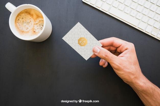 Mock up of hand halten visitenkarte mit kaffee und tastatur Kostenlosen PSD