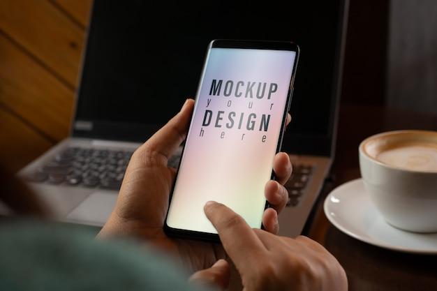 Modell bildschirm smartphone. schließen sie herauf hände unter verwendung des modernen intelligenten telefons in der kaffeestube Premium PSD
