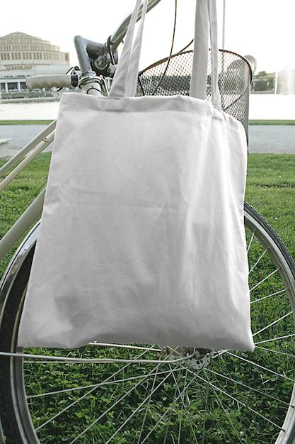 Modell der straßenstadt-taschengewebe-leinen-eco tasche, die am fahrrad sommerszene in der im freien hängt Premium PSD