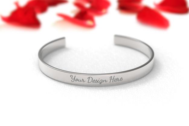 Modell des silberfarbenen metallarmbandes auf weißem hintergrund mit rosenblättern. Premium PSD