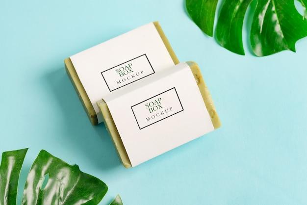 Modellpaket mit zwei seifenwickelboxen mit olivenölseife, isoliert auf blauem hintergrund mit palmblättern Premium PSD