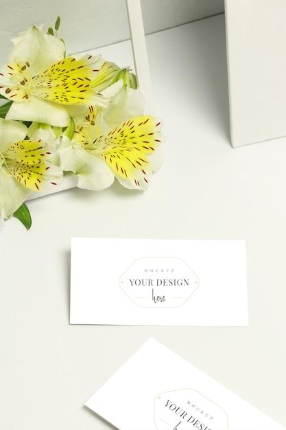 Modellvisitenkarten auf weißem hintergrund, frischen blumen und rahmen Premium PSD