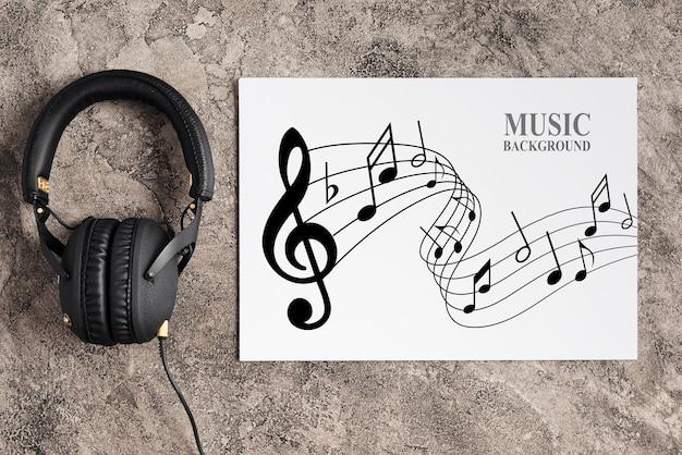 Musikdesign auf blatt mit kopfhörern dazu Kostenlosen PSD