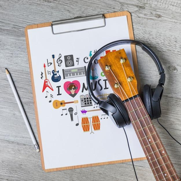 Musikmodell mit gitarre auf klemmbrett Kostenlosen PSD