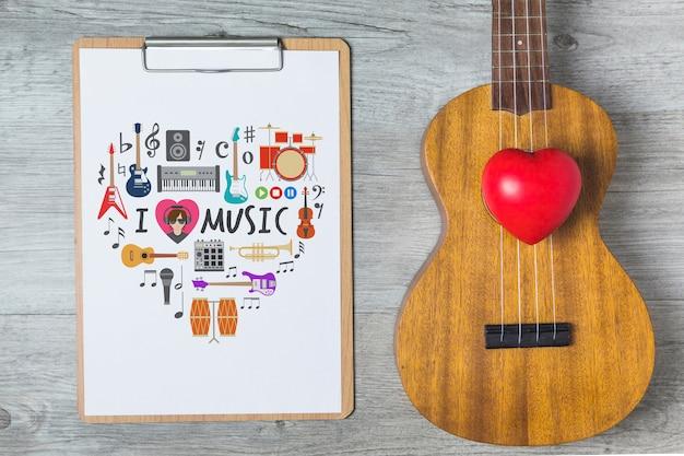 Musikmodell mit gitarre und klemmbrett Kostenlosen PSD