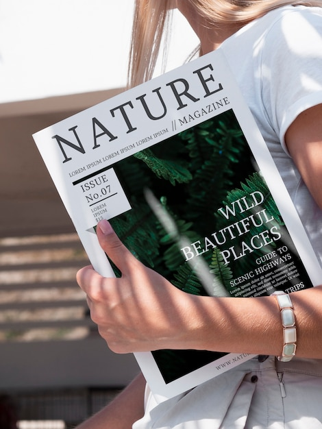 Nahaufnahmehand, die einen naturzeitschriftenspott hochhält Kostenlosen PSD