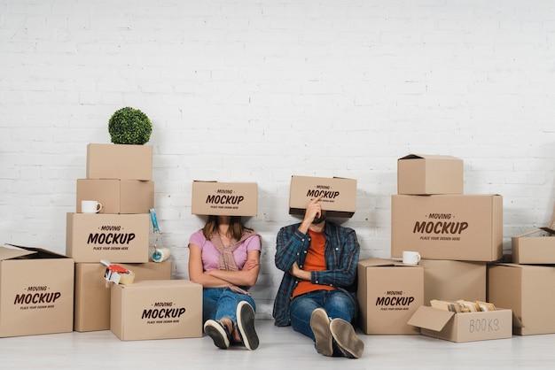Paar posiert albern mit beweglichen kisten über ihren köpfen Kostenlosen PSD