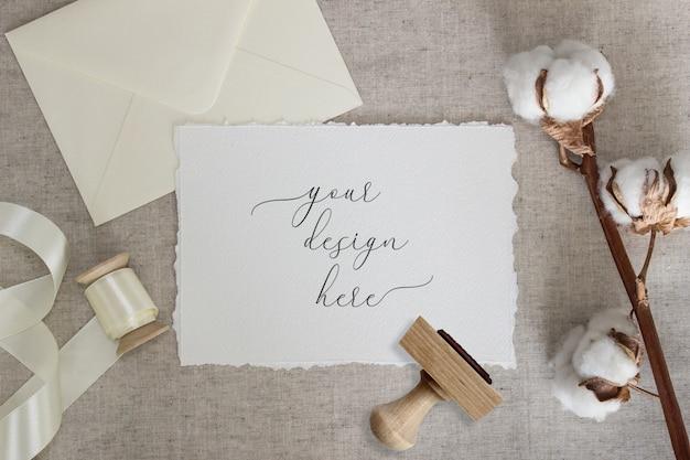 Papierkarte mit zerrissenem rand auf leinentuch mit baumwollblumen und seidenband. hochzeit briefpapier modell. einladung Premium PSD