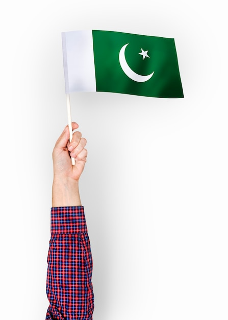 Person, die die flagge der islamischen republik von pakistan wellenartig bewegt Premium PSD