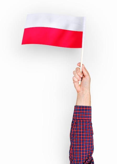 Person, die die flagge der republik von polen wellenartig bewegt Premium PSD