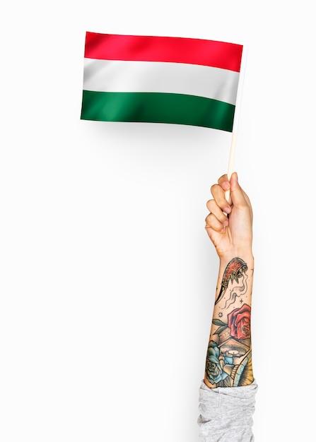 Person, die die flagge von ungarn wellenartig bewegt Premium PSD