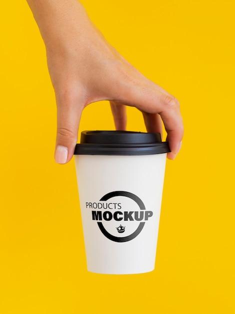 Person, die ein weißes kaffeetassenmodell hält Kostenlosen PSD