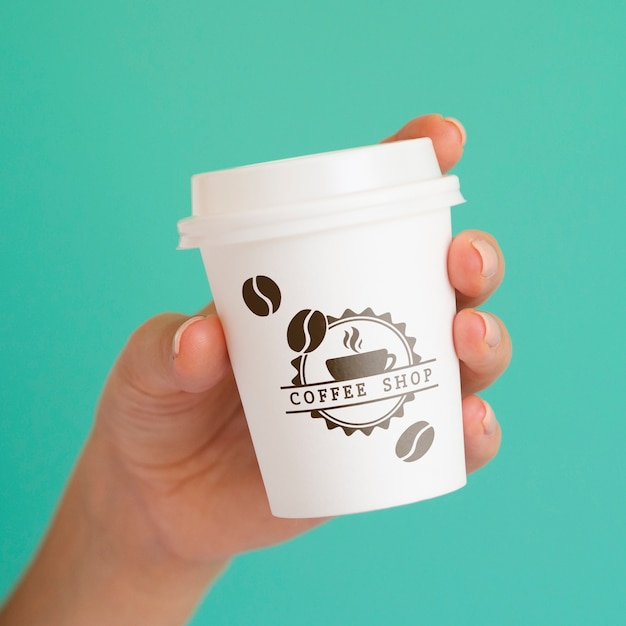 Person, die eine kaffeepapiertasse auf blauem hintergrund hält Kostenlosen PSD