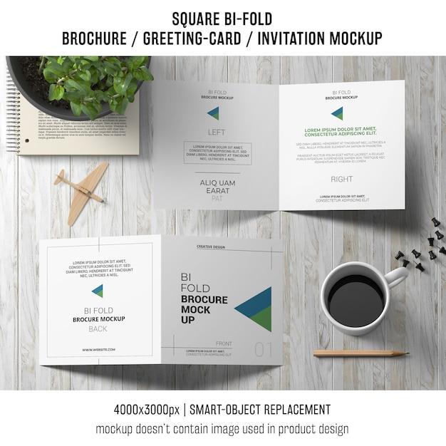 Quadratisches bi-fold broschüren- oder grußkartenmodell auf der hölzernen tischplatte Kostenlosen PSD