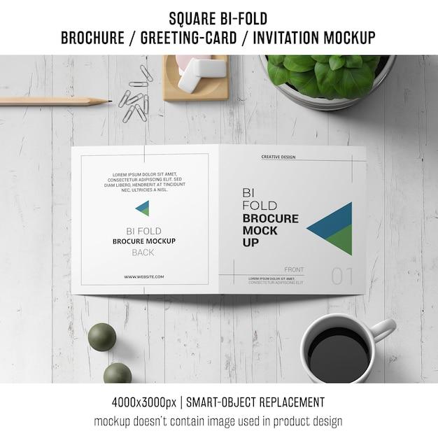 Quadratisches bi-fold broschüren- oder grußkartenmodell auf hölzernem arbeitsplatz Kostenlosen PSD