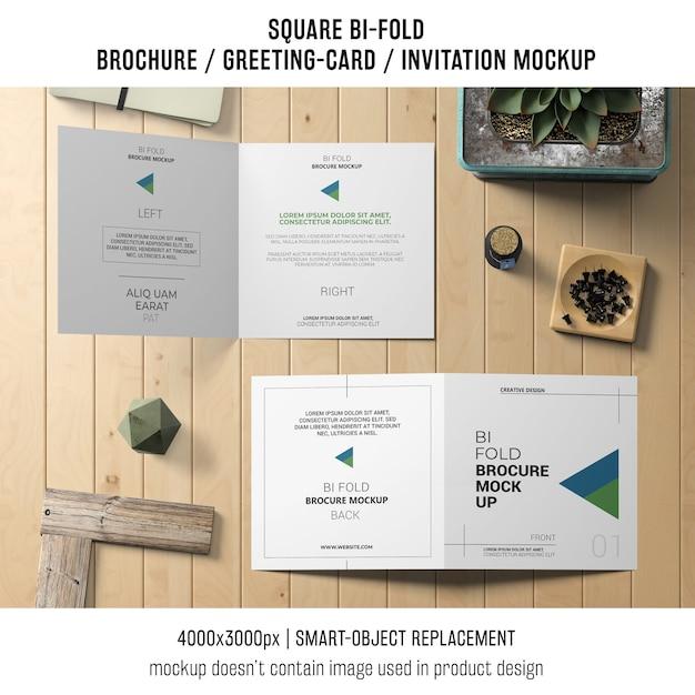Quadratisches bi-fold-broschüren- oder grußkartenmodell auf holztisch Kostenlosen PSD