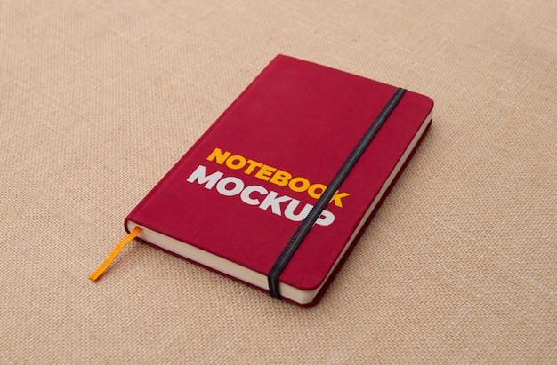 Rotes notizbuch auf stoffoberflächenmodell Kostenlosen PSD