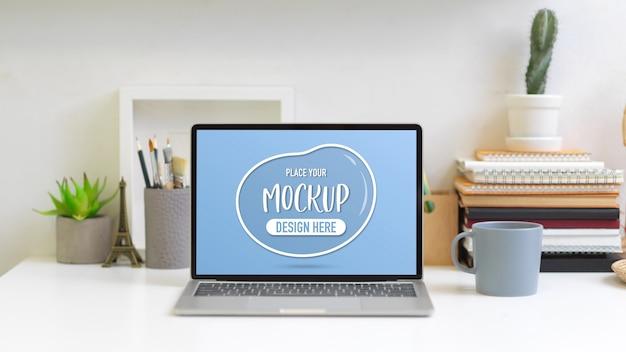 Schließen sie herauf ansicht des schreibtischs mit modell laptop, bücher, briefpapier und dekorationen Premium PSD