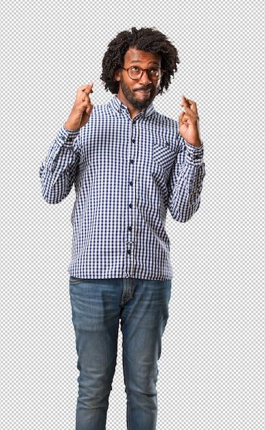 Schöner schwarzer mann mit gekreuzten fingern, wünscht sich glück für zukünftige projekte, aufgeregt, aber besorgt, nervöser ausdruck augen zu schließen Premium PSD