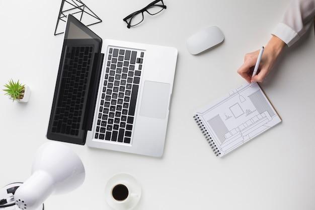 Schreibtisch mit laptop und mann, der auf notizbuchmodell schreibt Kostenlosen PSD